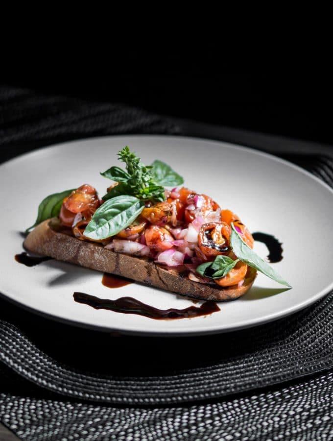 A dark contrast photo of roasted tomato bruschetta garnished with basil and balsamic glaze.