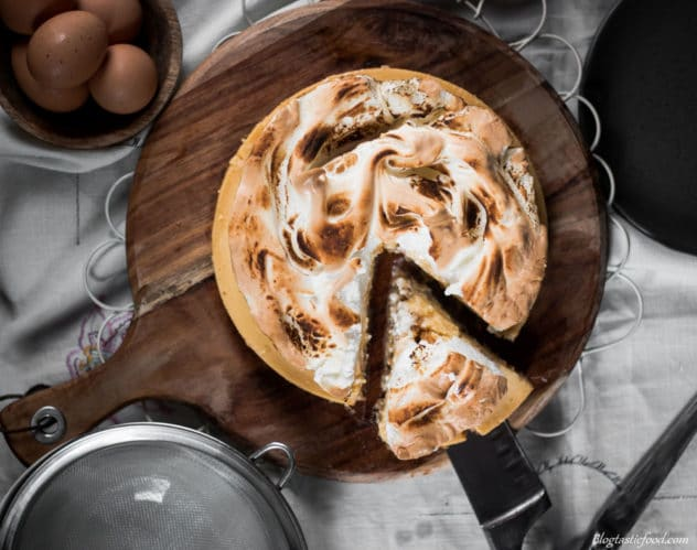 An overhead photo of a gluten free lemon meringue pie on a wooden board.
