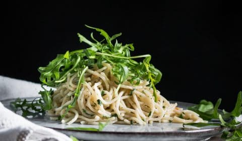 A plate of aglio e olio pasta with dressed rocket on top.