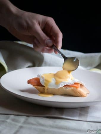 A photo of someone spooning hollandaise sauce on top of a poached egg.