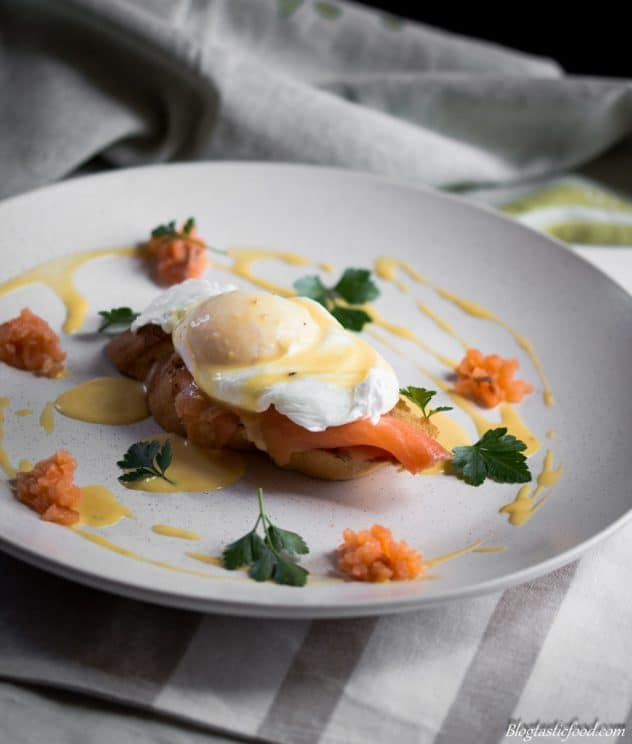 A photo of smoked salmon eggs benedict served on a toasted slice of baguette.