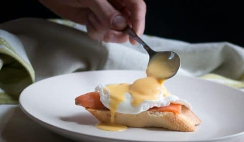 Holloandaise sauce getting spooned over a poached egg and smoked salmon.