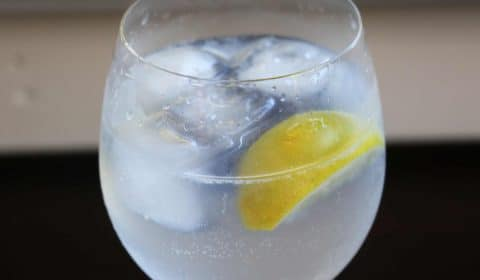 A macro photo of a glass of gin and tonic.