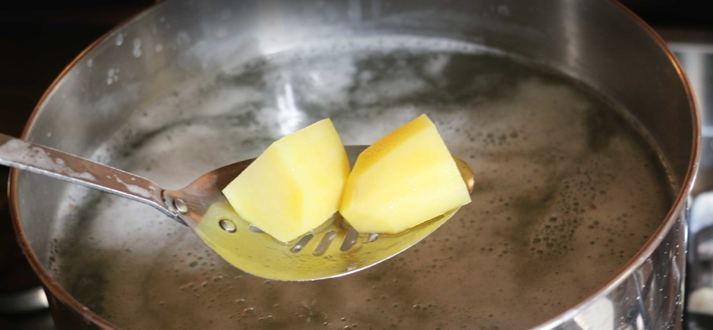 A slotted spoon scoping potatoes out of boiling water.