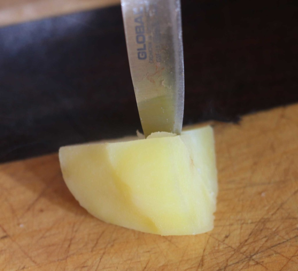 a small knife going into a dice of cooked potato.