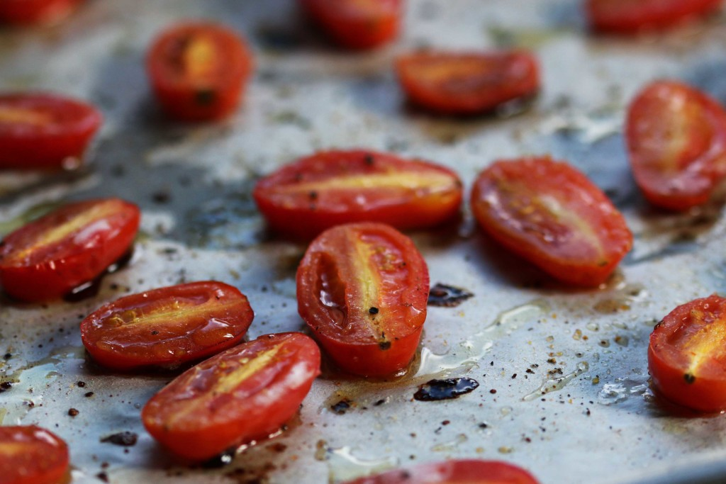 A close up of roasted tomatoes on a tray.