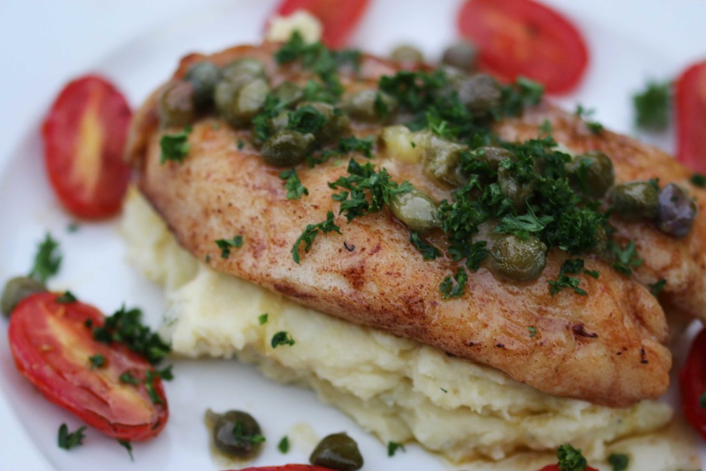 a close of of pan fried snapper on mash potato with roasted cherry tomatoes around the side of the plate.