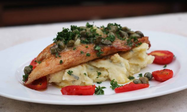 A buttery sauce served over pan fried snapper, mash potato and roasted cherry tomatoes.
