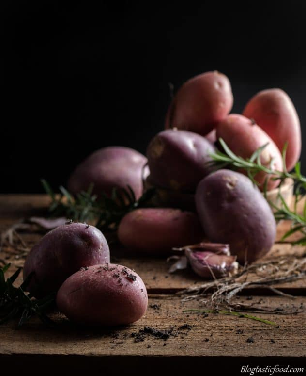 A dark, contrast photo of raw potato on a wooden board with dirt scattered around.