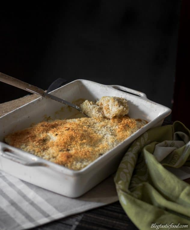 Vegan potato gratin with a golden browned panko breadcrumb topping served in a baking tray with a large spoon scooping out some of the potato.