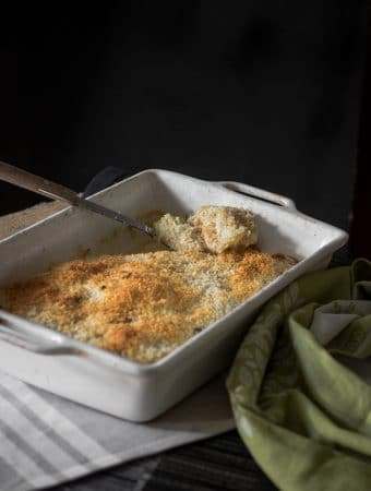 A photo of vegan potato gratin with panko breadcrumb topping served in a baking tray with a large spoon scooping out some of the potato.