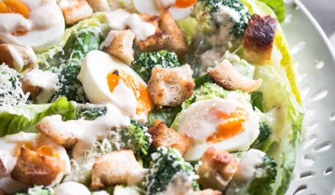 A close up photo of broccoli Caesar salad with spiced Caesar dressing on a nice big white platter.