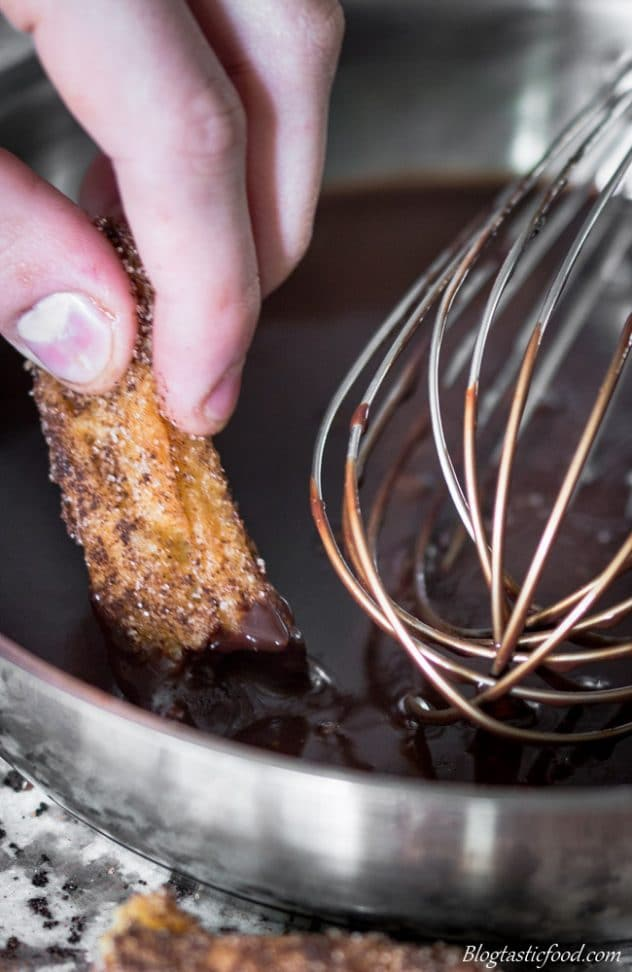 A photo of a churro being dipped into chocolate sauce.