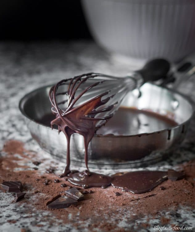 A photo of chocolate sauce dripping off of a whisk.