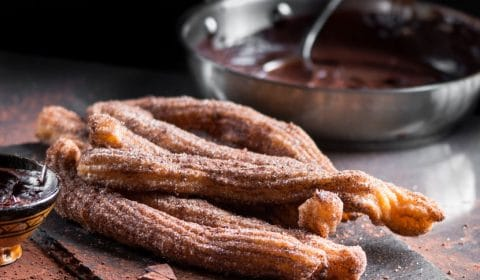 Churros served on a dark sushi platter with a pan of chocolate sauce in the background.