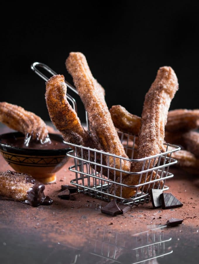 A dark, contrast photo of churros served in a small metal chip basket with cocoa dusted around.