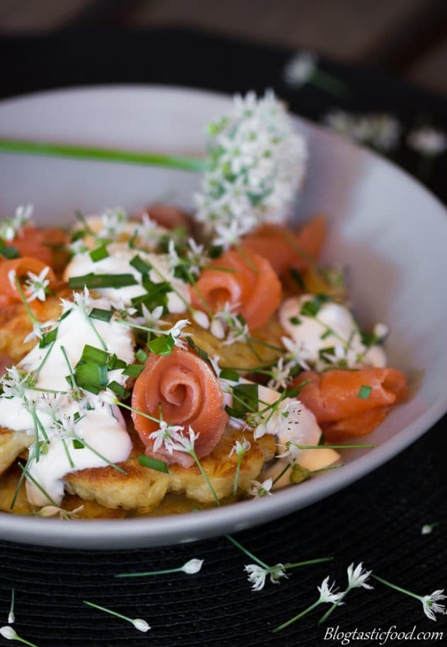 A photo of crispy potato cakes topped with sour cream and chives and smoked salmon.