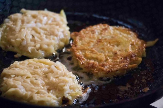 A photo of raw potato cakes being fried in a non-stick pan.