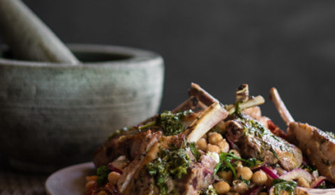 A photo of lamb cutlets served on chickpea salad, with a pestle mortar in the background.