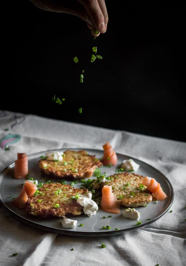 Fresh chives being sprinkle over a plate of potato cakes, sour cream and smoked salmon.