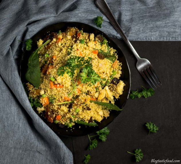 A photo of lemon, saffron and chicken couscous on a black plate garnished with parsley.