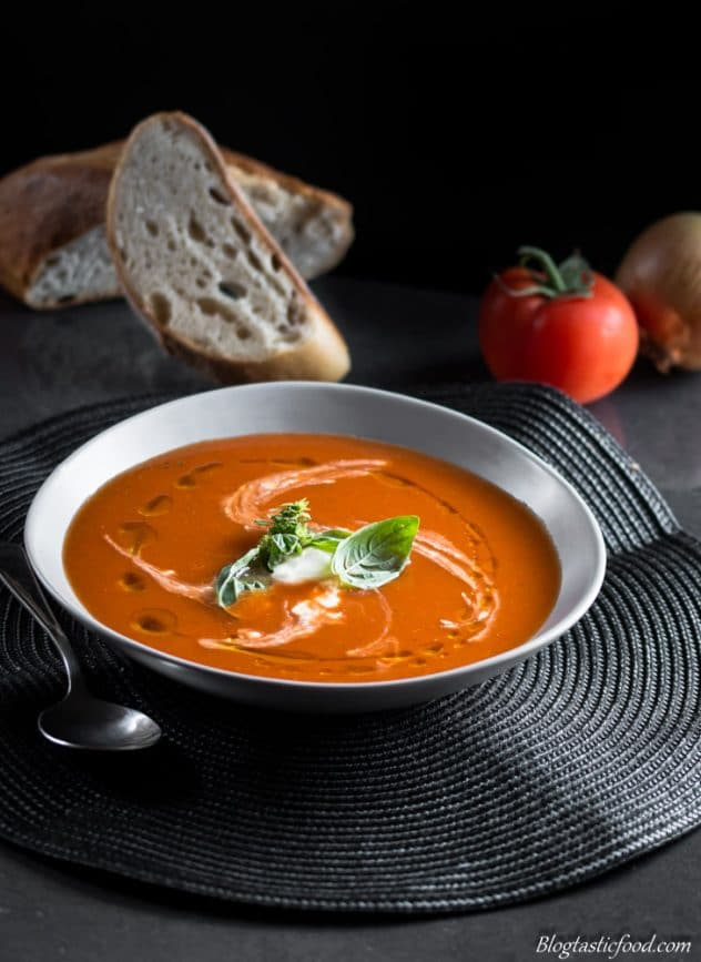 A bowl of spicy tomato soup with bread, an onion and a fresh tomato in the background.