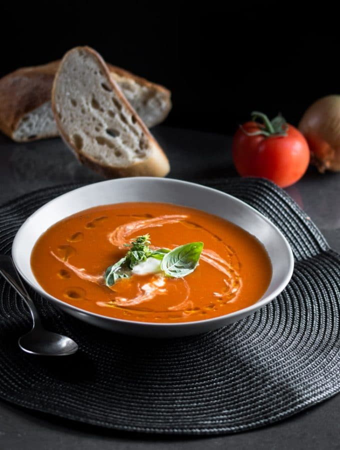 a dark moody photo of a bowl of spicy tomato soup garnished with sour cream and fresh basil leaves.