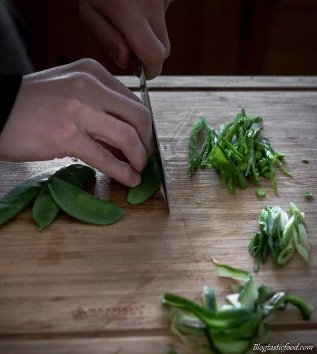 Some cutting snow peas julienne style on a chopping board.