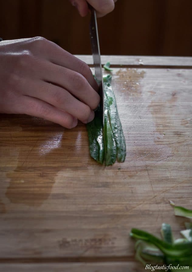 Slices of cucumber being cut julienne style.