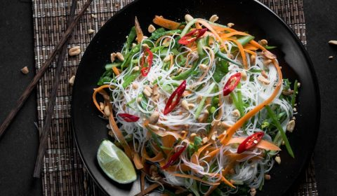 A photo of an Asian rice noodle salad that has been garnished with a wedge of lime, sliced chilli and toasted crushed peanuts.