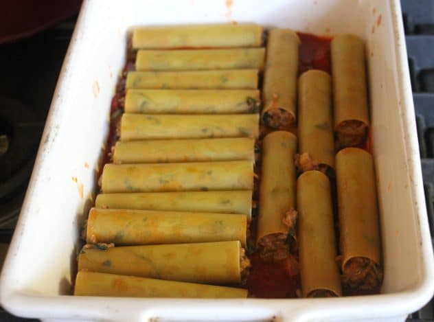 Uncook cannelloni stuffed with a beef filling on top of tomato sauce in a tray.