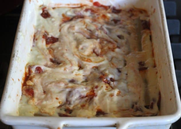 Beef filled cannelloni with bechamel sauce and tomato sauce on top.