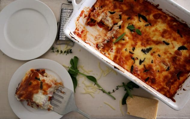A photo of a portion of cannelloni being transferred from a baking tray to a white plate.