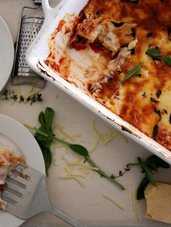 A overhead photo of cannelloni in a baking tray being served on a plate.