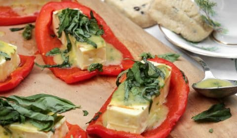 A photo of roasted red peppers with grilled halloumi cheese garnished with basil.
