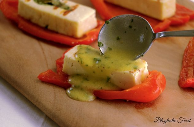 Dressing being spooned over grilled halloumi cheese and roasted red peppers.