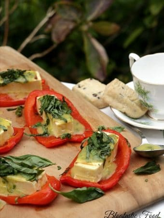 Roasted red peppers with grilled halloumi cheese served on a chopping board.