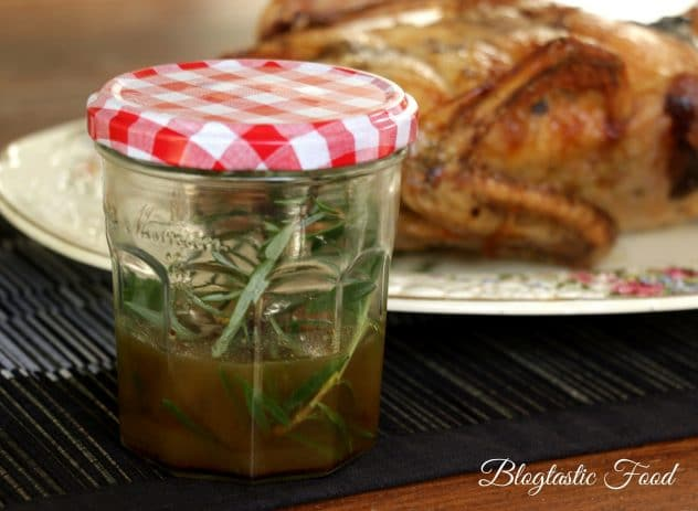 A photo of the fat leftover from a roasted duck stored in a jar with rosemary.
