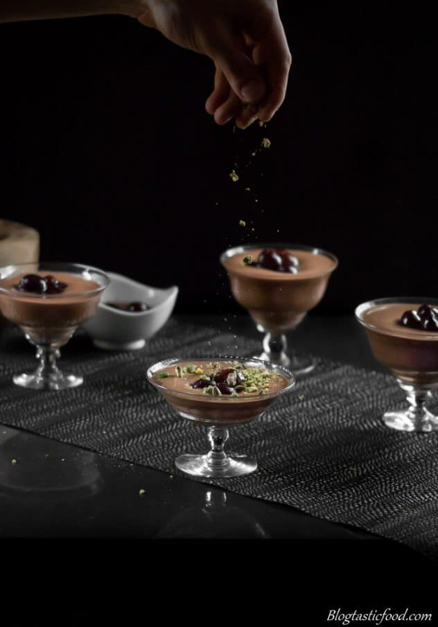 A dark, moody photo of someone sprinkling pistachios over mint chocolate mousse in dessert glasses.