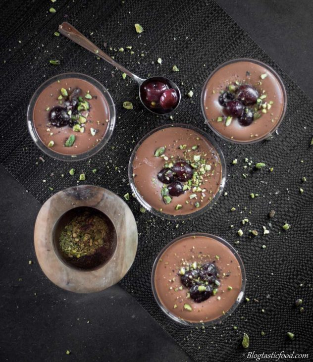 A overhead photo of chocolate mousse in glasses with cherries and crushed pistachios on top.