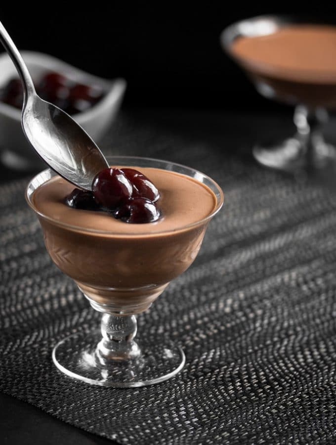 Alcohol Soaked Cherries being spooned over a glass filled with mint chocolate mousse.