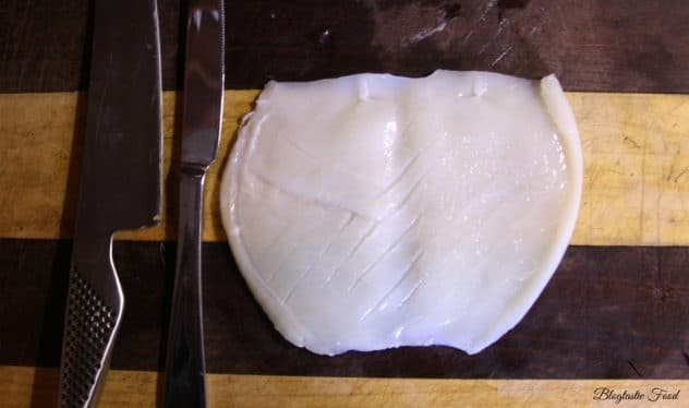 Raw squid on a cutting board that has been scored with a knife.