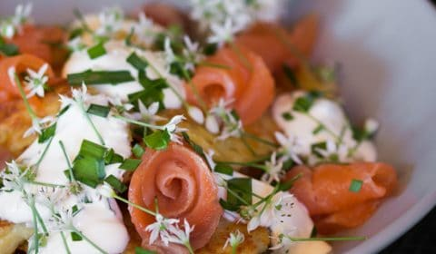 Potato Cakes served in a bowl with smoked salmon sour cream and chive flowers.
