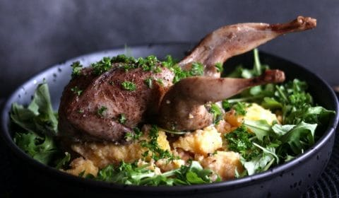 A photo of someone garnishing polenta and roasted quail in a black bowl with chopped parsley.