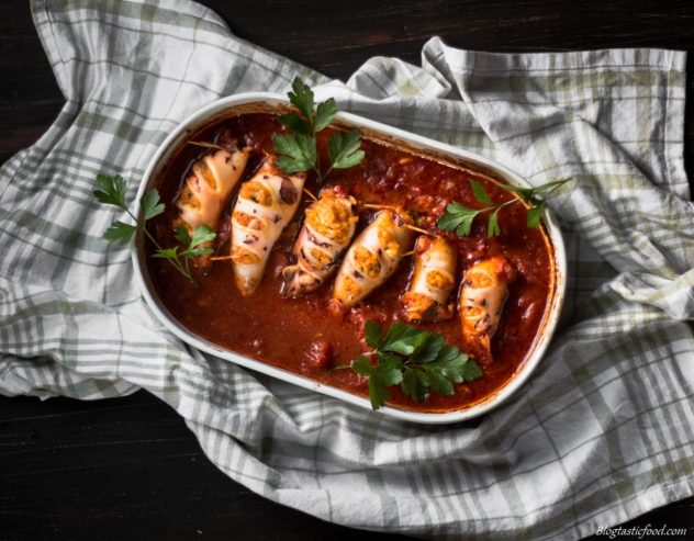 A photo of risotto stuffed squid in a baking tray filled with tomato sauce.