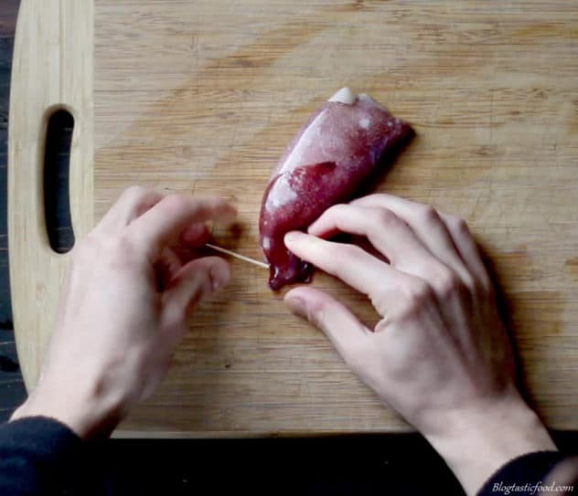 A photo of someone putting a toothpic through a squid tube stuffed with risotto.