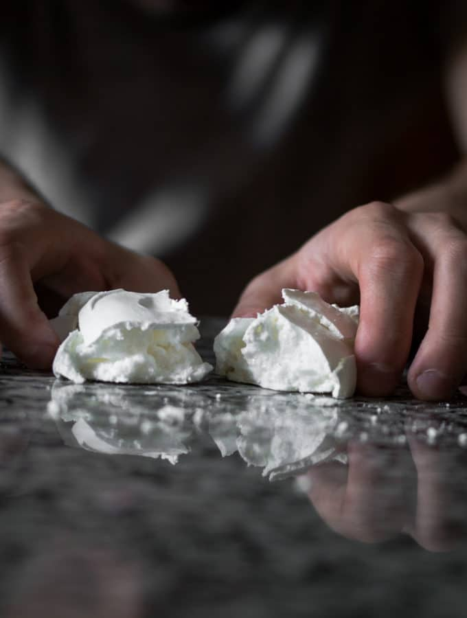 Some breaking a meringue in half on a table.