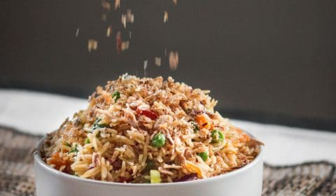 Some crispy fried shallots getting sprinkled over a nice big bowl of vegetable fried rice.