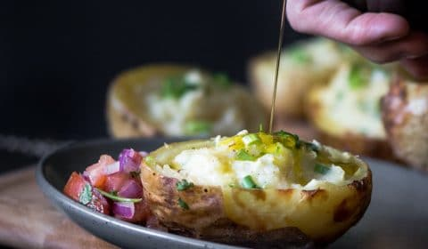 A dark moody photo of someone drizzling extra virgin olive oil over twice baked potatoes served with fresh salsa.