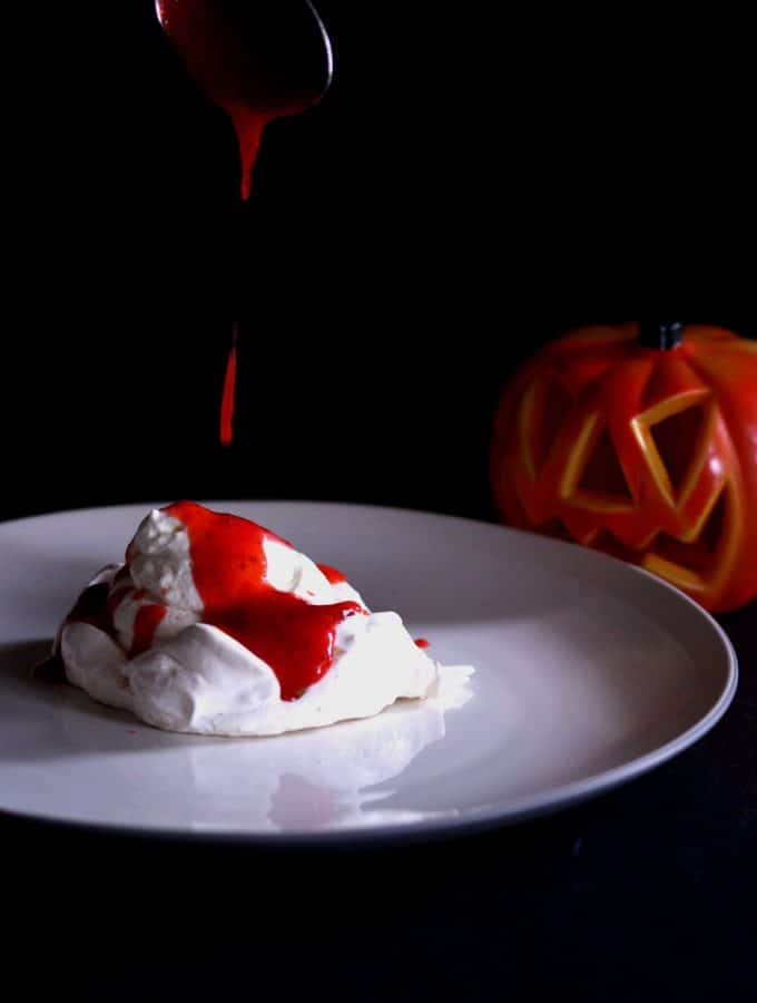A photo of strawberry coulis being dripped on a meringue to resemble blood for Halloween.